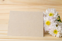 White chrysanthemum flowers with blank note paper on wooden back. Ground Royalty Free Stock Photo