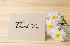 White chrysanthemum flowers with thank you card on wooden table. White chrysanthemum flowers with thank you card on wooden background Stock Photo