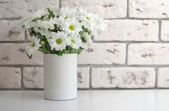 White chrysanthemums in a vase on a stone background. Flowers on the table close-up stock photography