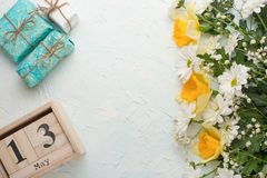 White chrysanthemums and yellow narcissus on a wooden background with a calendar on which May 13, the International Mother`s Day royalty free stock photo