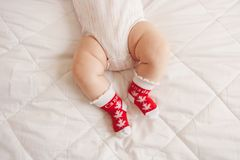 white chubby baby legs feet wearing red socks with Canadian maple leaf flag royalty free stock photography