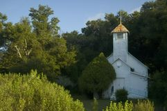 White church. An abandoned looking country church tucked into a group of trees stock photos