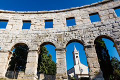 White Church and Ancient Roman Amphitheater. White Church Framed in the Arch of Ancient Roman Amphitheater in Pula, Istria, Croatia Royalty Free Stock Photo