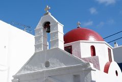 White church architecture in Mykonos, Greece. Chapel with bell tower and red dome. Church building on blue sky. Summer. Vacation on mediterranean island Stock Images