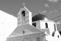 White church architecture in Mykonos, Greece. Chapel with bell tower and red dome. Church building on blue sky. Summer. Vacation on mediterranean island stock photos