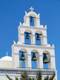 White church bell tower against blue sky in Greece Royalty Free Stock Image