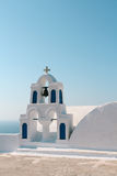 White church bell tower with blue sky in Oia, Santorini, Greece Stock Image