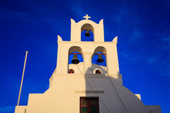 White church and bell tower in Santorini, Greece. Santorini, Greece - White church with blue dome on sky background Stock Photos