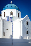 White church with blue dome and Greek flag, Santorini Stock Photography