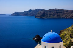 White church with blue dome in Santorini, Greece. Santorini, Greece - White church with blue dome and caldera view Stock Photos