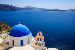 White church with blue dome in Santorini, Greece. Santorini, Greece - White church with blue dome and caldera view Stock Images