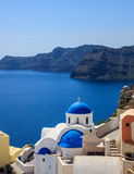 White church with blue dome in Santorini, Greece. Santorini, Greece - White church with blue dome and caldera view Royalty Free Stock Image