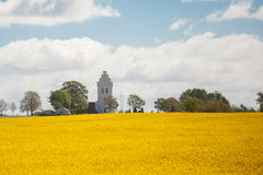 A white church with a field of rapeseed in the foreground Stock Photography