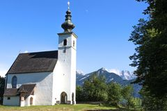 White church in front of the Alps stock photography