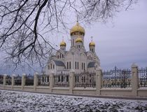 White Church with Golden domes on a gloomy autumn day. Siberian city royalty free stock photo