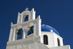 White Church on the Greek Island of Santorini. Looking skyward at a white Santorini, Greece church.  There are three church bells and a blue dome with a clear Royalty Free Stock Photography