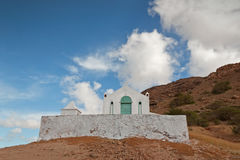 White Church. A White Church with Green Door Against a Cloudy Blue Sky Stock Image