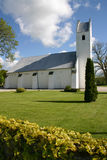 White church lawn. White danish christian church with lawn and hedge in foreground stock photo