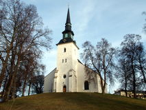 White church. Lindesbergs church with trees and a blue sky Stock Images