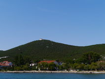 A white church on a mountain on the isle Ist. The village Ist on the island Ist in the Adriatic sea of Croatia stock images
