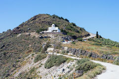 White church on mountain between of towns on Santorini island Stock Photography