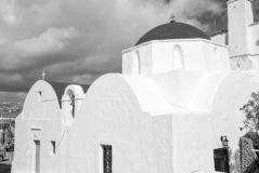 White church in Mykonos, Greece. Church with red dome on cloudy blue sky. Chapel building architecture on sunny outdoor. Religion and cult concept. Summer stock images