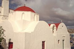 White church in Mykonos, Greece. Church with red dome on cloudy blue sky. Chapel building architecture on sunny outdoor royalty free stock photography