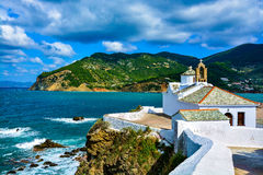 White church over the bay on a cloudy day, Skopelos, Greece Stock Photos
