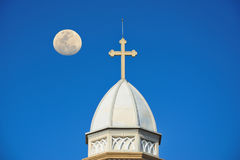 The white church roof has a cross, with the moon and the sky as Stock Photography