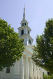 White Church Steeple. Pristine New England white church steeple set against beautiful blue sky - Tower has clock set into it.  Front has Doric columns. built Stock Image