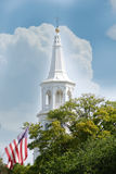 White church steeple in downtown Charleston, South Carolina. White church steeple with a white puffy cloud, flag and a tree in downtown Charleston, South Royalty Free Stock Photo