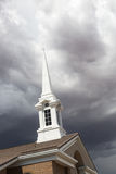 White Church Steeple Tower Below Ominous Stormy Thunderstorm Clouds. Stock Photos