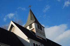 White church with steeple under repair under deep blue sky. Clapboard church, black tar shingle roof, cirrus white Royalty Free Stock Photo