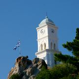 White church tower and greek flag against blue sky Stock Photography