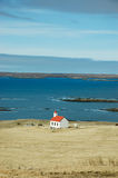 White church, turquoise sea, hayfield, Iceland. A white church with red roof located alone on the hayfield at the turquoise seaside with blue sky on sunshine day Stock Image