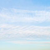 White cirrus clouds in blue afternoon sky Stock Image
