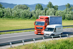 White Citroën van overtakes red MAN truck on slovak D1 highway in countryside. Royalty Free Stock Photo
