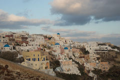 White city on a slope of a hill at sunset, Oia, Santorini, Greec Stock Photography