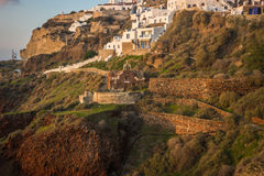 White city on a slope of a hill at sunset, Oia, Santorini, Greec Royalty Free Stock Photos