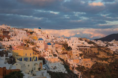 White city on a slope of a hill at sunset and pink clouds, Oia, Stock Images