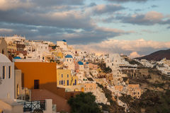 White city on a slope of a hill at sunset and pink clouds, Oia, Stock Photography