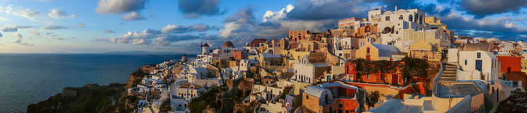 White city on a slope of a hill at sunset and pink clouds, Oia, Royalty Free Stock Image