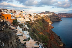 White city on a slope of a hill at sunset and pink clouds, Oia, Stock Image