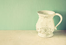 White classic and antique vase on wooden table. filtered image Royalty Free Stock Image