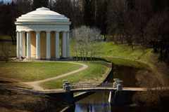 White classic arbor with columns in a beautiful park with paths and a bridge across a stream, horizontal Stock Photo
