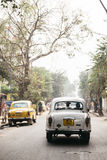 White classic car run on the street with trees in Kolkata, India. Stock Photography