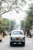 White classic car run on the street with trees in Kolkata, India. Stock Photo
