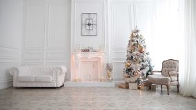 White classic Christmas and New Year interior. Room with fireplace, green tree decorated and retro grey chair stock footage