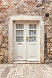 White classic door in ancient stone building Royalty Free Stock Images