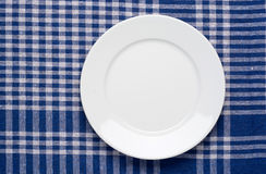 White classic plate on blue checkered tablecloth Royalty Free Stock Images